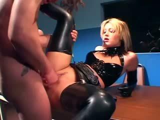 Sīka auguma blondīne uz a policists uniforma un spīdošas lateks veļa jāšanās par a galds