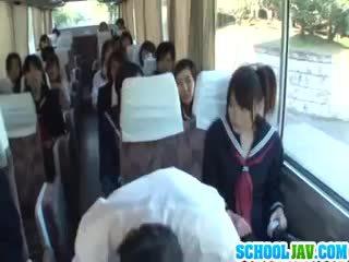 Pusaudze par a publisks autobuss puts viņai seja uz a autobuss rider lap