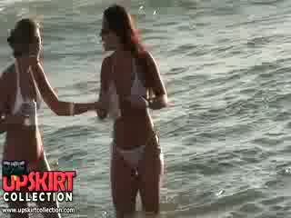 Charming bikini chicks are staying in the water talking and having no idea to be spied