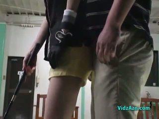 Ázijské dievča giving fajčenie na ju knees pre ju golf instructor
