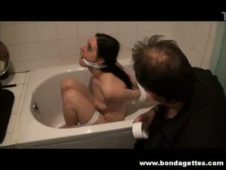 Bath bondage of submissive Honesty Cabellero in gagged restraints and wet toilet