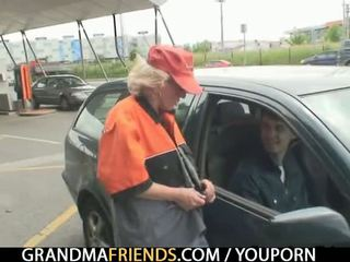 Old woman swallows two cocks outdoors