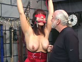 Brunete uz a korsete ar blindfold gets viņai vāvere tortured ar clamps