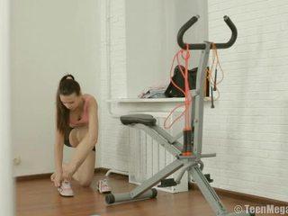 Dünn teen puts auf trainingseinheit clothes im fitnesscenter